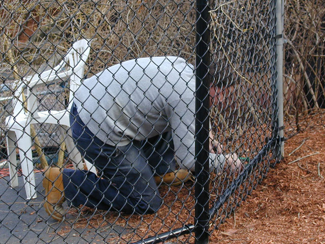 How can I further secure the bottom of a chain link fence